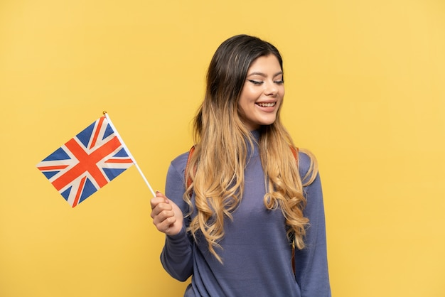 Young russian girl holding an united kingdom flag isolated on yellow background looking side
