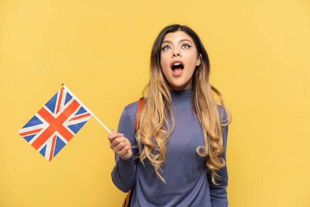 Young russian girl holding an united kingdom flag isolated on yellow background looking up and with surprised expression