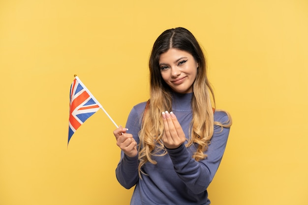 Young russian girl holding an united kingdom flag isolated on yellow background making money gesture