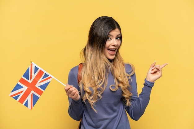 Young russian girl holding an united kingdom flag isolated on yellow background pointing finger to the side and presenting a product