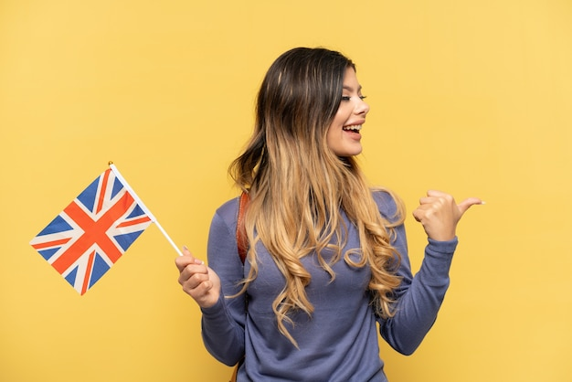 Young russian girl holding an united kingdom flag isolated on yellow background pointing to the side to present a product