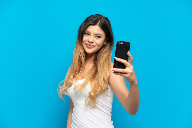 Young russian girl isolated on blue background making a selfie