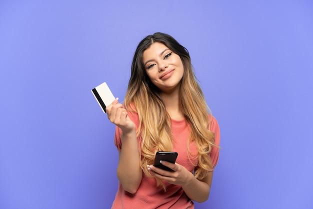 Молодая русская девушка изолирована на синем фоне, покупая с мобильного с помощью кредитной карты, думая