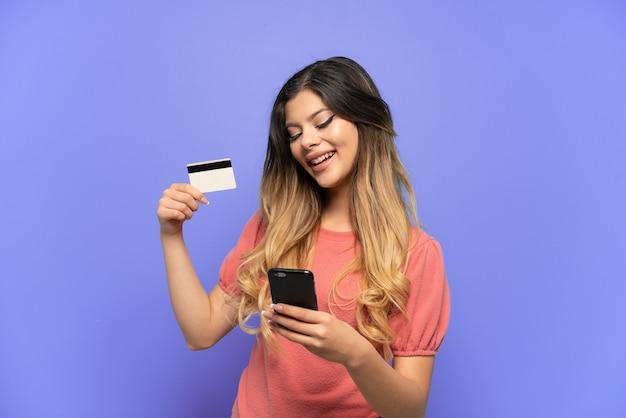 Молодая русская девушка изолирована на синем фоне, покупая с мобильного с помощью кредитной карты