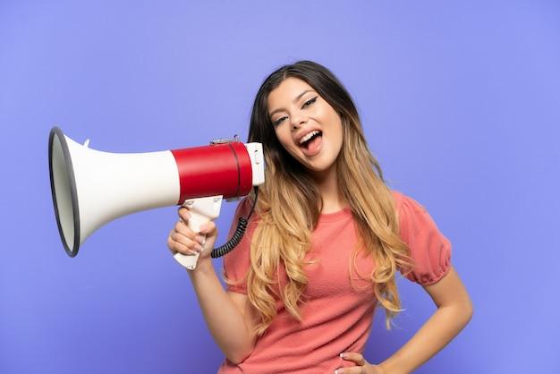 Молодая русская девушка изолирована на синем фоне с мегафоном и улыбается