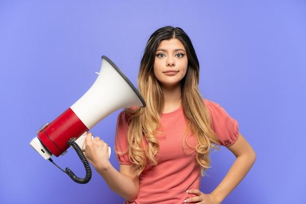 Молодая русская девушка, изолированная на синем фоне, держит мегафон с подчеркнутым выражением лица