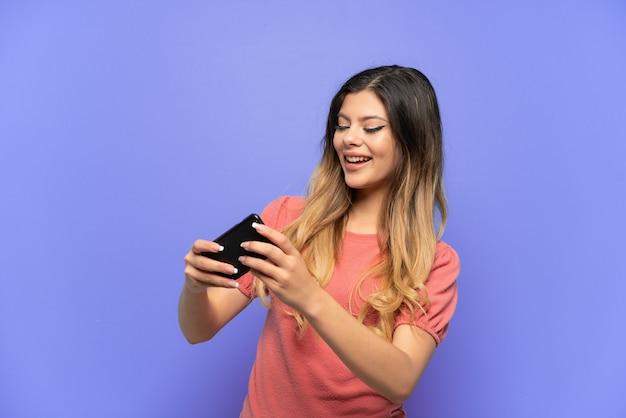 携帯電話で遊んで青い背景で隔離の若いロシアの女の子