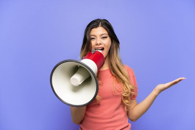 Молодая русская девушка, изолированная на синем фоне, кричит в мегафон и указывает сторону