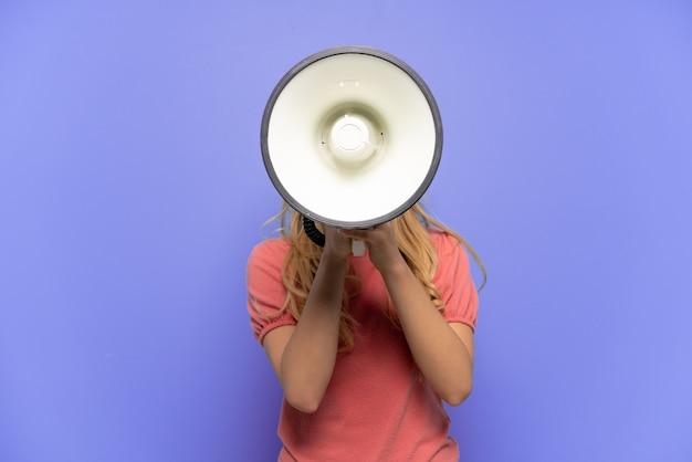 Молодая русская девушка, изолированная на синем фоне, кричит в мегафон, чтобы что-то объявить