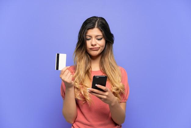Молодая русская девушка изолирована на синей стене, покупая мобильный телефон с помощью кредитной карты, думая