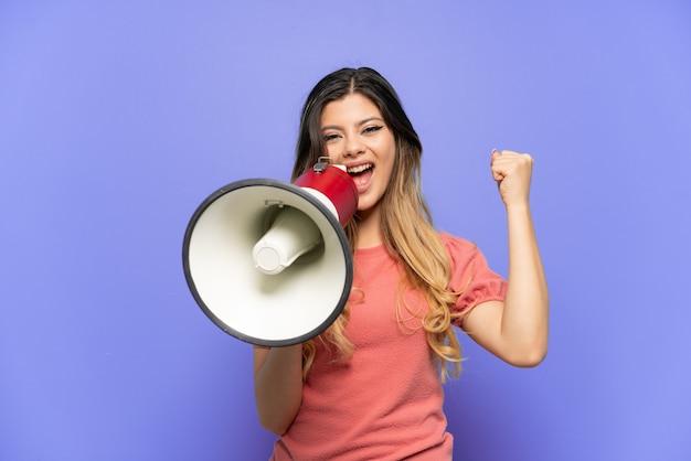 Молодая русская девушка изолирована на синей стене, кричит в мегафон и указывает сторону