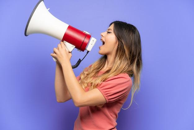 Молодая русская девушка, изолированная на синей стене, кричит в мегафон, чтобы объявить что-то в боковом положении