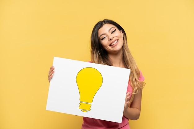 電球のアイコンが付いたプラカードを保持し、それを指している黄色の背景で隔離の若いロシアの女の子
