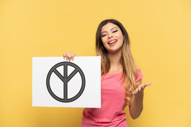 Молодая русская девушка изолирована на желтом фоне, держа плакат с символом мира с большим пальцем вверх