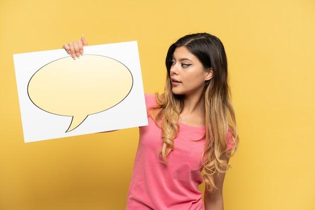 Молодая русская девушка изолирована на желтом фоне с плакатом с речевым пузырем