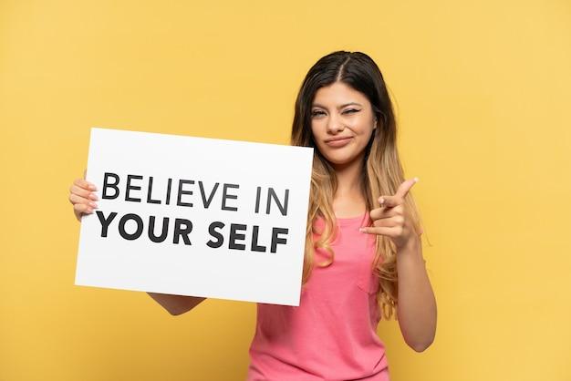 Молодая русская девушка, изолированная на желтом фоне, держит плакат с текстом «верь в себя» и указывает вперед