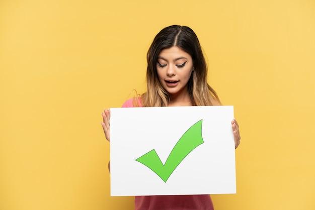 텍스트 녹색 확인 표시 아이콘이 있는 플래카드를 들고 노란색 배경에 고립 된 젊은 러시아 소녀