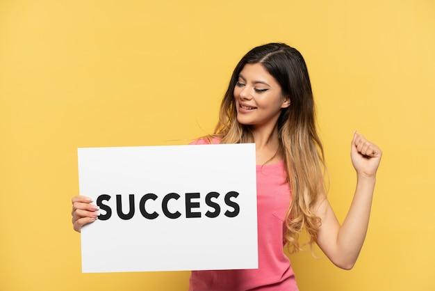 노란색 배경에 격리된 러시아 소녀는 success라는 문구가 적힌 플래카드를 들고 승리를 축하했습니다.