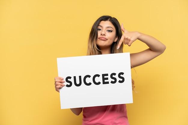 노란색 배경에 격리된 어린 러시아 소녀는 성공이라는 문구가 적힌 플래카드를 들고 그것을 가리키고 있습니다.