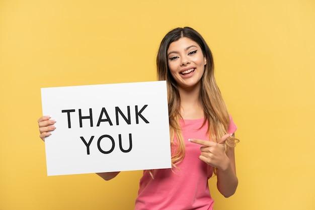 Молодая русская девушка изолирована на желтом фоне, держа плакат с текстом спасибо и указывая на него