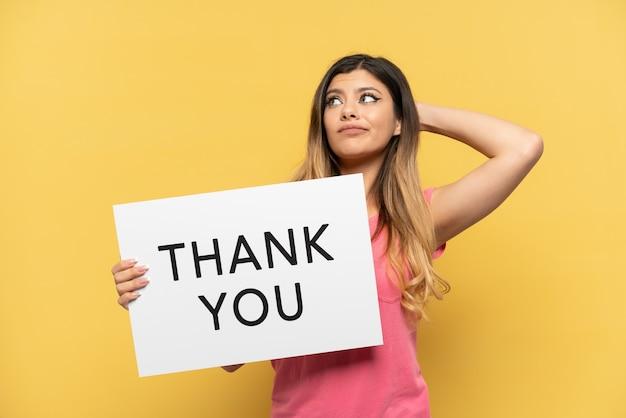 노란색 배경에 격리된 러시아 소녀는 감사합니다라는 문구가 적힌 플래카드를 들고 생각하고 있습니다.
