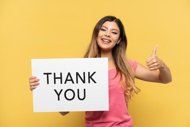 Молодая русская девушка изолирована на желтом фоне держит плакат с текстом спасибо с большим пальцем вверх