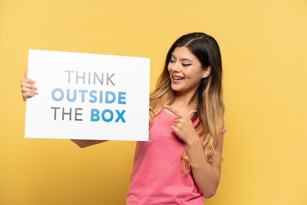 黄色の背景に分離された若いロシアの女の子は、テキストのプラカードを保持し、ボックスの外側を考えて、それを指しています