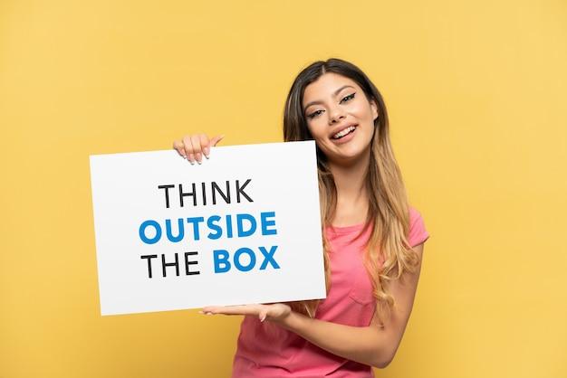 テキストとプラカードを保持している黄色の背景で隔離の若いロシアの女の子幸せな表現でボックスの外を考える