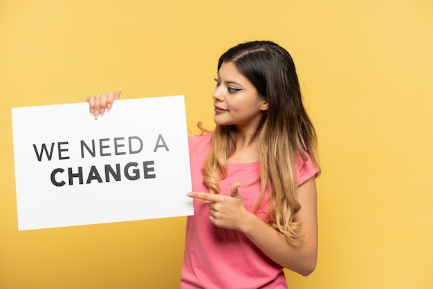 Молодая русская девушка изолирована на желтом фоне, держа плакат с текстом «нам нужны перемены» и указывая на него
