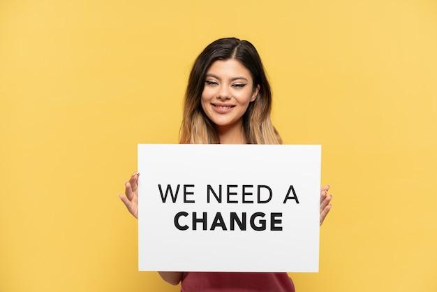 Молодая русская девушка, изолированная на желтом фоне, держит плакат с текстом «нам нужны перемены» со счастливым выражением лица