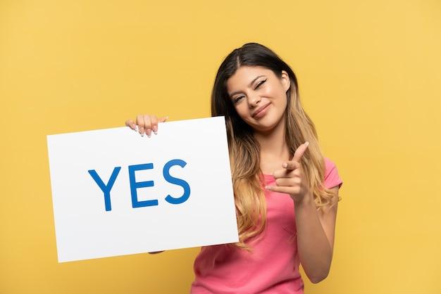 노란색 배경에 격리된 러시아 소녀는 yes라는 문구가 적힌 플래카드를 들고 앞을 가리키고 있다