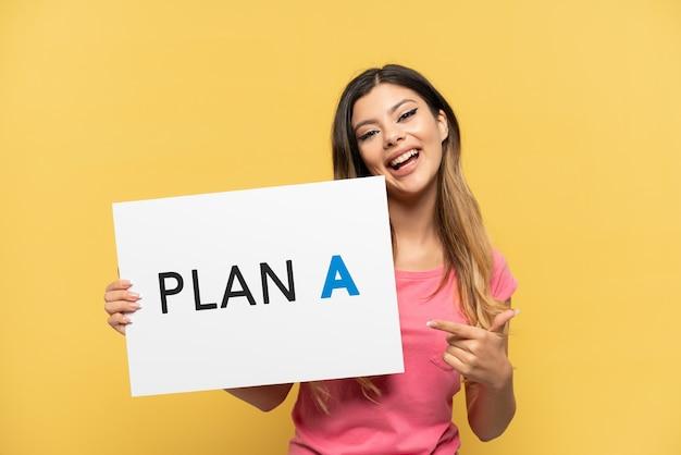 노란색 배경에 격리된 러시아 소녀는 plan a라는 메시지가 적힌 플래카드를 들고 그것을 가리키고 있다