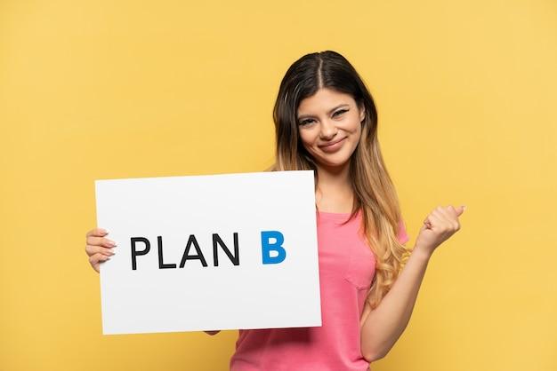 Молодая русская девушка изолирована на желтом фоне, держит плакат с сообщением план b и сердится