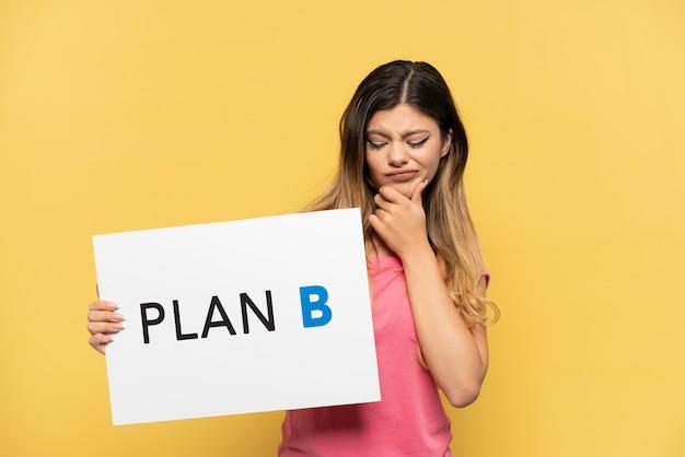 Молодая русская девушка изолирована на желтом фоне, держа плакат с сообщением план b и думая