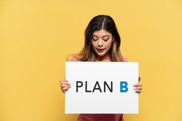 노란색 배경에 격리된 어린 러시아 소녀는 plan b라는 메시지가 적힌 플래카드를 들고 있습니다.
