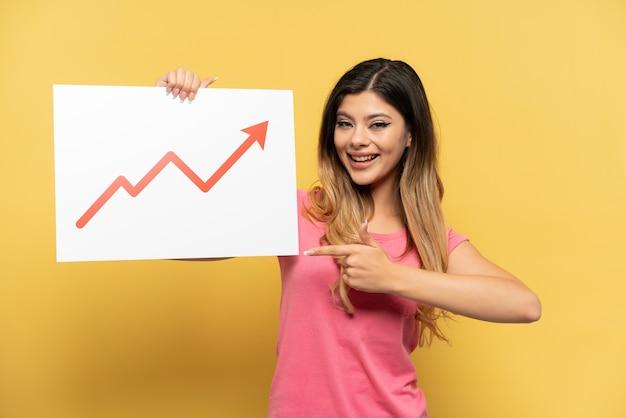 Молодая русская девушка изолирована на желтом фоне с табличкой с растущим символом стрелки статистики и указывая на нее