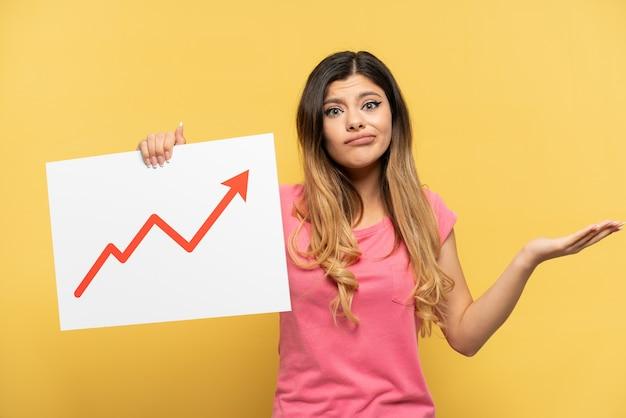 Молодая русская девушка изолирована на желтом фоне с табличкой с растущим символом стрелки статистики, имеющим сомнения