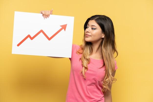 행복한 표정으로 성장하는 통계 화살표 기호가 있는 표지판을 들고 노란색 배경에 고립된 어린 러시아 소녀