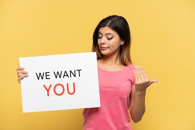 Молодая русская девушка, изолированная на желтом фоне, держит доску we want you и делает приближающийся жест