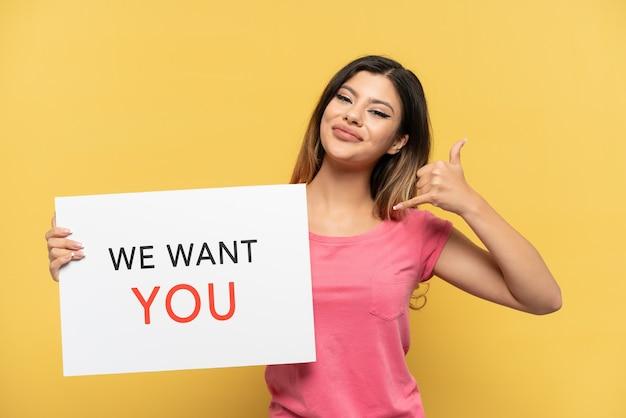 Молодая русская девушка, изолированная на желтом фоне, держит доску we want you и делает жест по телефону