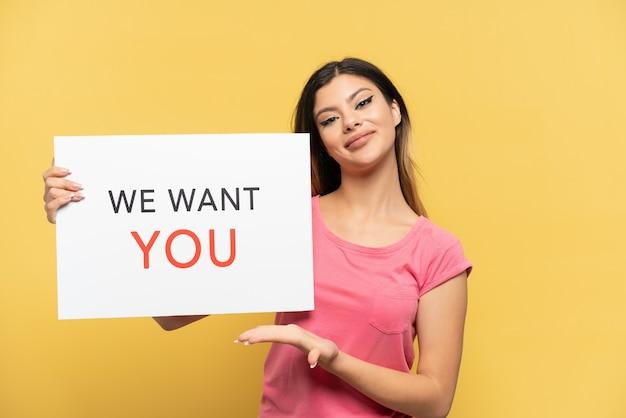 Молодая русская девушка изолирована на желтом фоне, держа доску we want you и указывая на нее