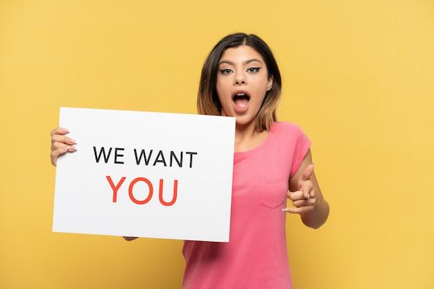 Молодая русская девушка изолирована на желтом фоне, держа доску we want you и указывая вперед