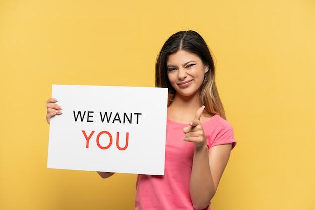 노란색 배경에 격리된 어린 러시아 소녀는 we want you 보드를 들고 앞을 가리키고 있습니다.