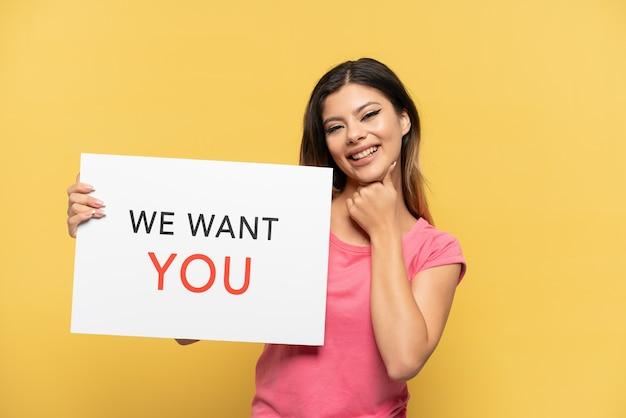 Молодая русская девушка, изолированная на желтом фоне, держит доску we want you и кричит