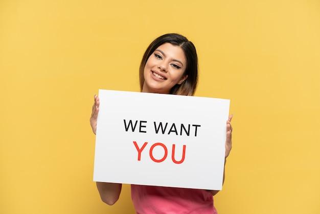Молодая русская девушка изолирована на желтом фоне, держа доску we want you с счастливым выражением лица