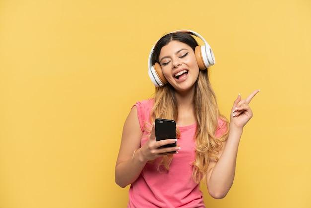 노란색 배경에 격리된 어린 러시아 소녀는 휴대전화와 노래로 음악을 듣고 있습니다.