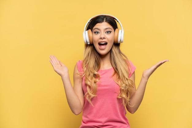 黄色の背景に孤立した若いロシアの女の子は驚いて音楽を聞い