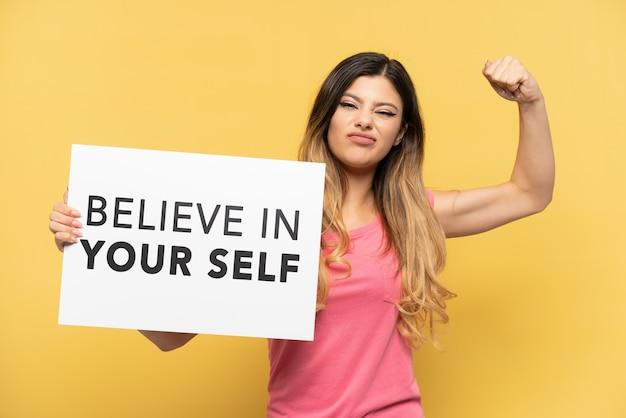 노란 벽에 고립된 어린 러시아 소녀는 자신을 믿으라는 문구가 적힌 플래카드를 들고 강한 몸짓을 하고 있다