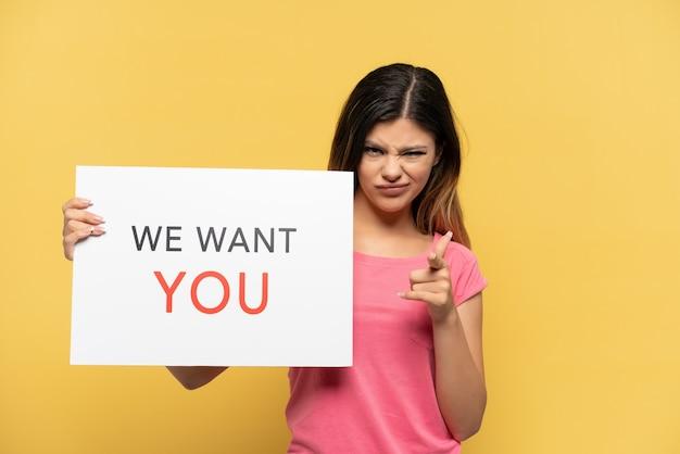 Молодая русская девушка изолирована на желтой стене, держа доску we want you и указывая на фронт