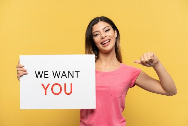 Молодая русская девушка изолирована на желтой стене с гордым жестом держит доску we want you
